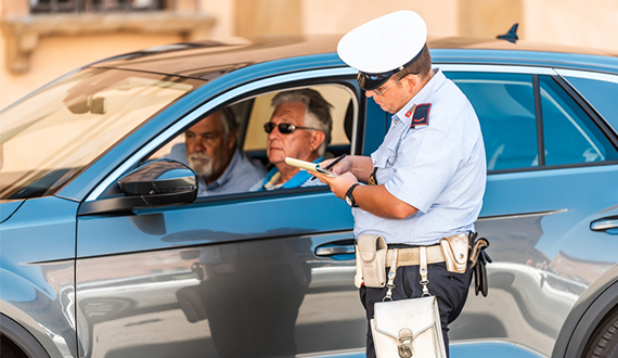 Carabinieri police officer attending to a car