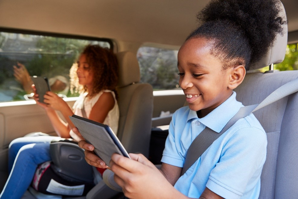 Children playing on their electronic devices in the car