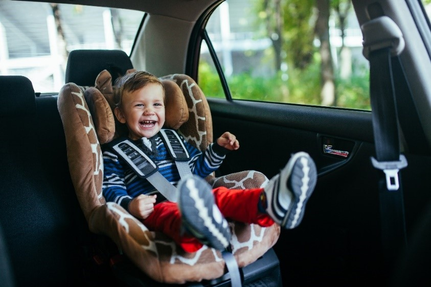 A happy toddler in a car seat