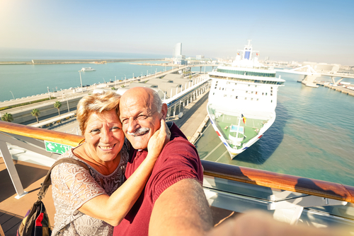 Couple taking a selfie in front of cruise ship