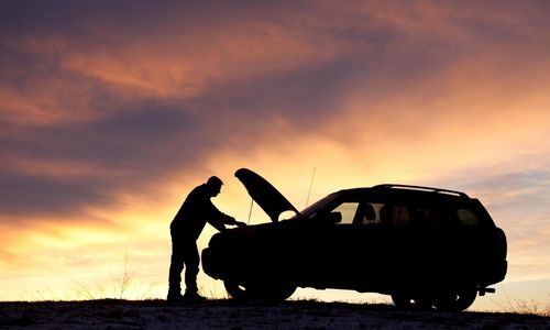man fixing a broken down car at sunset