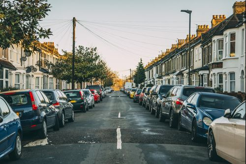 lots of cars parked on a street of houses in London