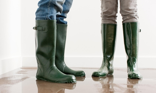 Two people standing in wellington boots in a flooded house